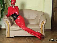 Sexy belle in red latex suit poses and provokes