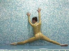 Flexible brunette in a shiny catsuit poses for you