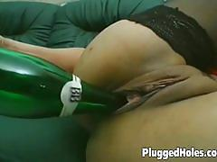 Brunette dildos her cunt with a bottle