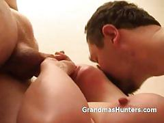 Busty granny sucking and fucking two eager cocks.
