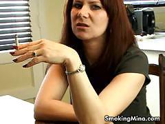 Seductive milf smoking while stripteasing
