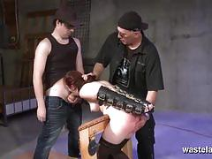 Two dungeon masters spanking their sex slave's ass