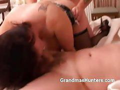 Tattooed brunette mature gets banged by two studs