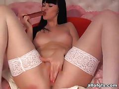 Hot brunette in white stockings dildos her cunt