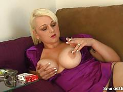 Smoking blonde exposes her round tits