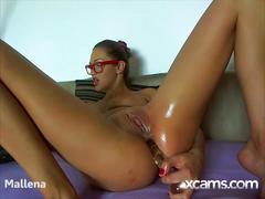 Gorgeous cam babe with sexy glasses fucks her ass with a huge glass dildo