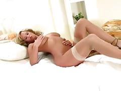 Big boobed blonde stripping and teasing on a bed