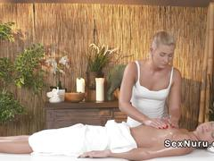 Blonde masseuse rubs brunettes cunt in massage room