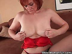 Mature redhead in black stockings fists her cunt