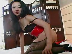 Asian masturbates in a corset and stockings