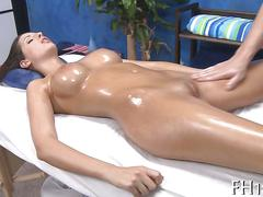 Oiled up brunette caressed and oiled by a pussy starved masseur