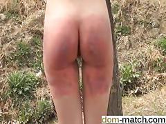 Little ass honey gets spanked outside tied to a post