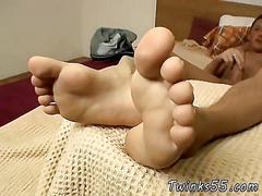 Skinny twink rubs his feet while tugging his boner in bed