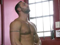 Hairy chested hunk rubs his big fat cock in a locker room