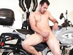 Horny biker jerks off next to his ride and strips