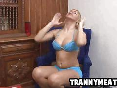 Busty tranny blonde wanking her cock off in a chair