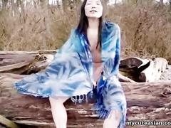 Asian slut is on the beach naked posing