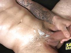 Tattooed stud works his big cock on a small couch