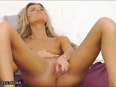 Skinny blonde strips and fucks with dildo