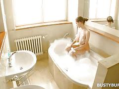 Busty beauty taking a foamy bath