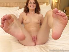 Sexy redhead gives a footjob and gets a cumshot on her feet