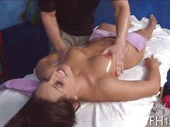 Oiled up babe gets her shaved pussy rubbed on massage table