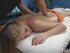 Shaved blonde beauty getting rammed doggy style on a massage table