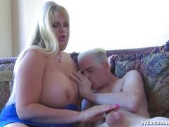 Huge-titted blonde strokes a young guy's cock