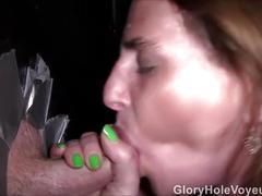 Redhead milf sucks two cocks in glory hole