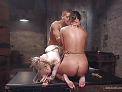Two female slaves are ordered around by the dominant master