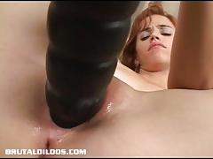 Redhead takes on colossal dildo