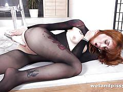 Redhead beauty plays with her piss