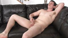 Hunk is on his coach stroking his large cock just for your satisfaction