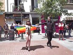 Brunette's pride parade with a dildo hanging on her neck
