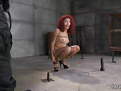 Gagged redhead sits on dildos in the basement