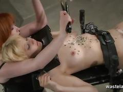 Redheaded mistress burns her blonde slave with wax