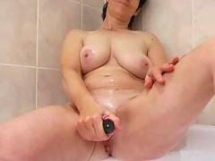 Mature babe toying in bathtub