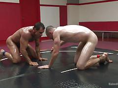 Oiled hunks wrestle