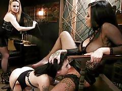 Dominated brunette licking the feet of her mistress