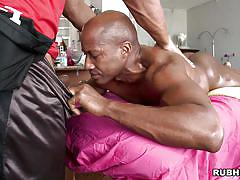 Oiled black man giving blowjob while being massaged