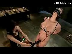 Girl with harness hanging getting electricty to her nipples pussy stimulated with vibrator by mistress in the dungeon