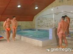 Five college gay guys having fun together in pool.