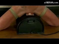 Busty blonde tied to handrail tortured with clips while sitting on electric vibrator whipped in the training room
