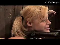 Slim blonde girl tied to wall getting her pussy fucked with fucksaw while tortured with clips and whip by the master in the dungeon