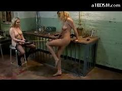 Blonde mistress stimulating herself with vibrator while torturing slave girl with electric stick in the dungeon
