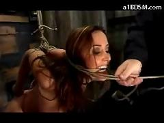 Busty girl tied arms weight hanging on her belt spanked with stick in the dungeon