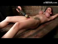 Busty tattooed girl tied legs and arms tits tortured with clips and rubber bands whipped pussy stimulated with vibrator in the dungeon