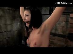 Girl with small tits standing with tied legs and arms whipped pussy stimulated with vibrator tortured with weight in the dungeon