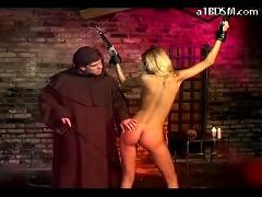 Blonde girl with tied arms hanging getting her pussy fingered fucked by monk in the dungeon