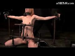 Slim girl tied to metal poles on her knees getting her pussy stimulated with vibrator nipples tortured with weights in the dungeon